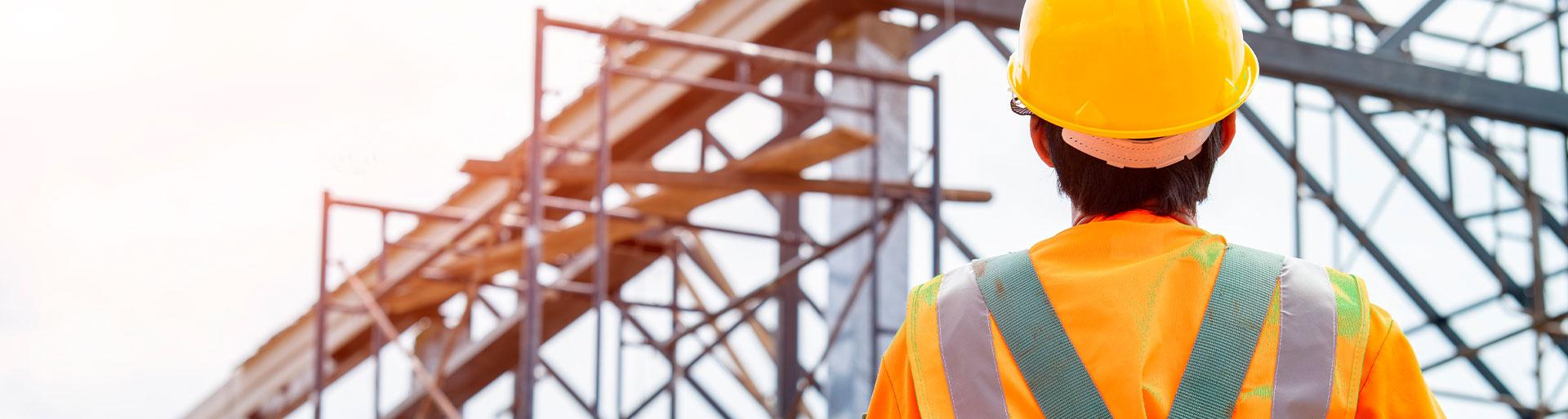 homem de costas em frente a um prédio em construção