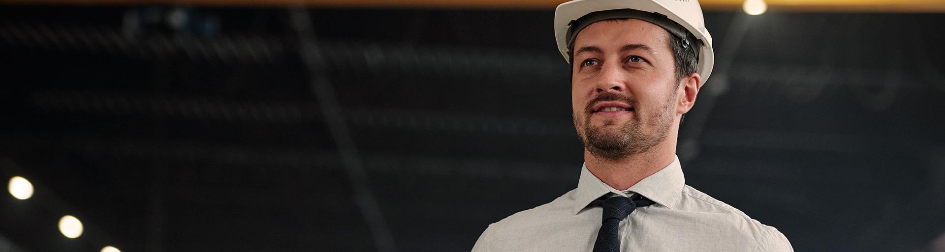 Homem branco com chapéu de construção branco na cabeça em uma obra.