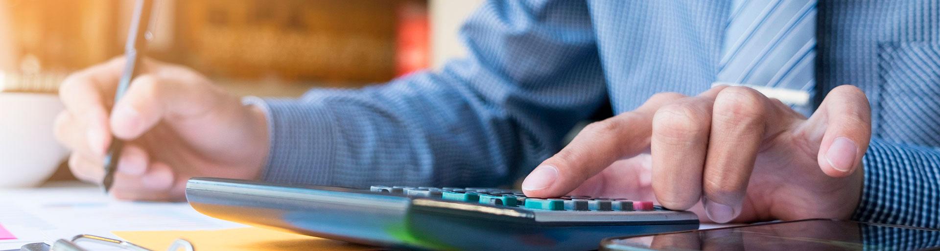 homem digitando em uma calculadora