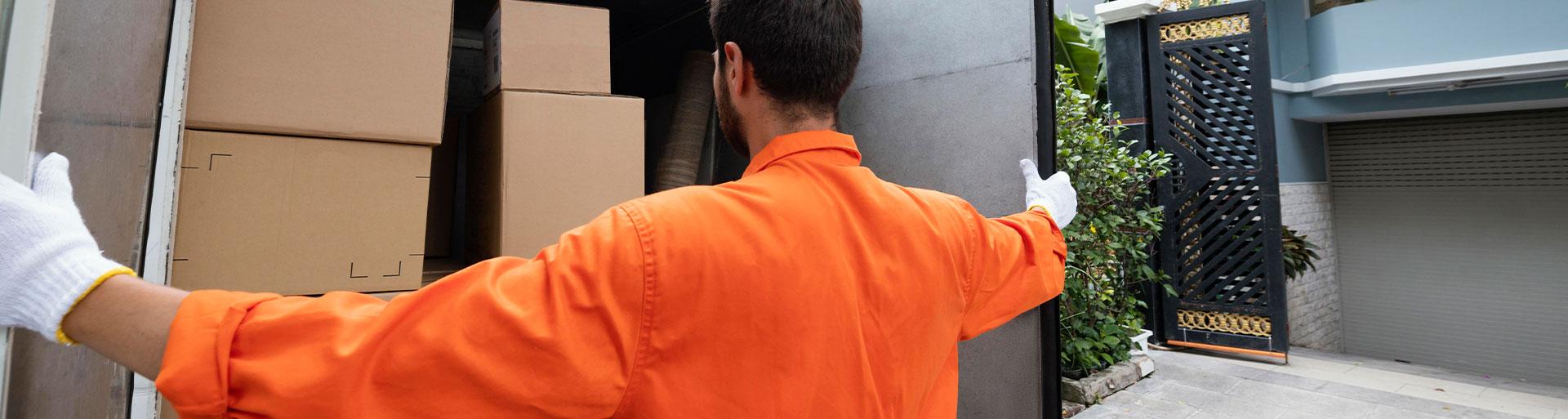 homem abrindo a porta de um caminhão com cargas