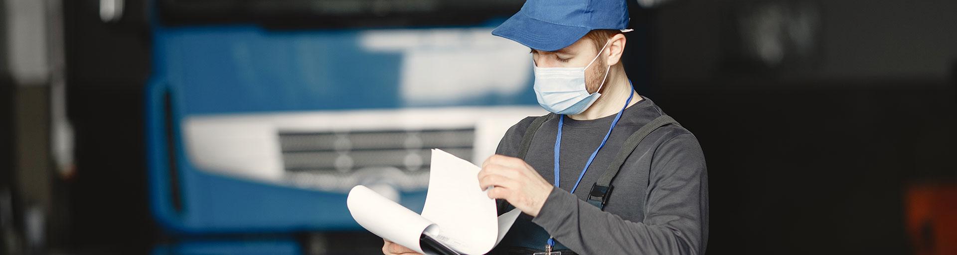 motorista com documento nas mãos em frente a um caminhão