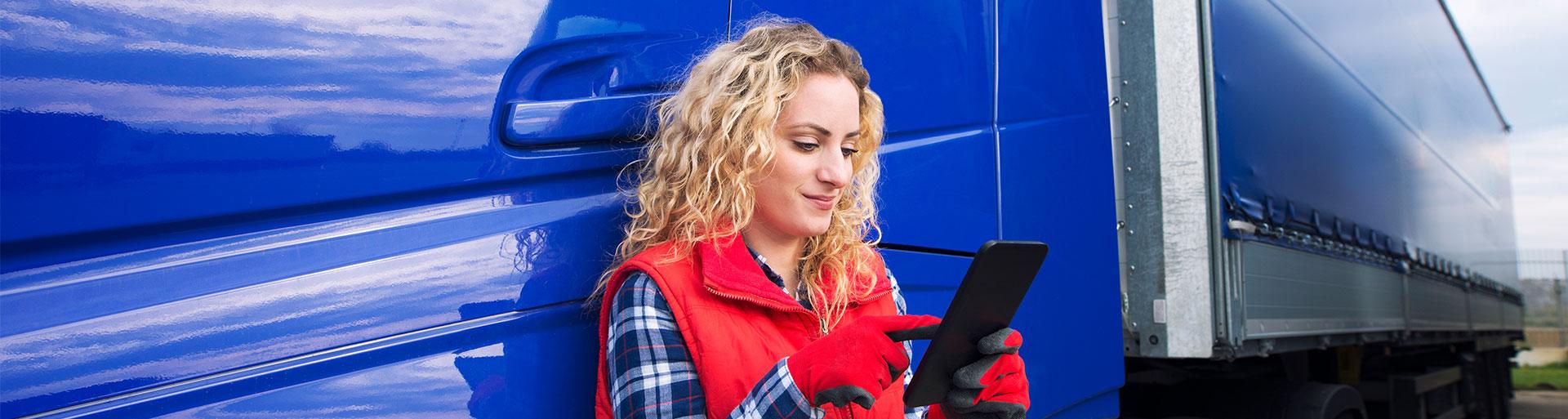 mulher com telefone na mão em frente a um caminhão